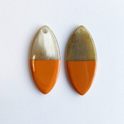Small oval buffalo horn pendant with orange lacquered part.