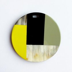 Round pendant geometrical motifs buffalo horn and beige , yellow and black lacquer..